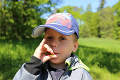 Small boy in baseball cap blowing to the footstalk Royalty Free Stock Image