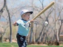 Small boy with bat and ball. Small boy wearing baseball cap swinging bat at baseball Stock Photo