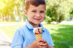 Small boy with beautiful eyes holding ice-cream in the park. Royalty Free Stock Photo