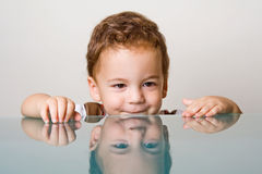 Small boy behind glass table Royalty Free Stock Photos