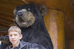 Small boy and big bear Stock Image