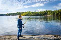 Small boy with big fishing rod Stock Image