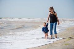 Small boy and big girl walking on seaside stock image