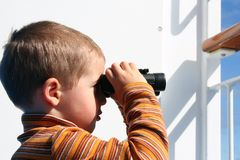 Small boy with binoculars. Smal boy with binoculars on a balcony Royalty Free Stock Image