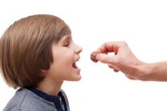 A small boy bites chocolate ball from man hand Royalty Free Stock Images