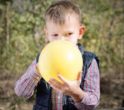 Small boy blowing up a colorful yellow balloon Stock Photos