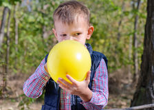 Small boy blowing up a colorful yellow balloon Royalty Free Stock Photography