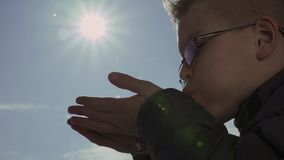 Small boy blows snowflakes from his hands against the blue sky with sun stock video footage