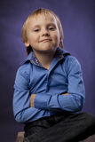 Boy in a blue shirt and black trousers on purple background Stock Photo