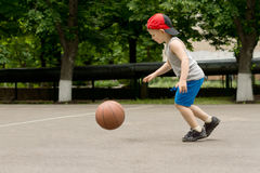 Small boy bouncing a basketball on a court Royalty Free Stock Images