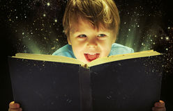Small boy carrying a magic book royalty free stock photography