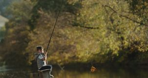 Small boy with charismatic face playing with a rod till his teaching how to catch the fishes. stock footage