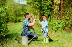 Small boy child help father in farming. Eco farm. father and son in cowboy hat on ranch. use watering can and pot. Garden equipment. happy earth day. Family royalty free stock photography