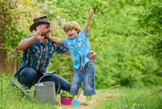 Small boy child help father in farming. happy earth day. Family tree nursering. Eco farm. watering can, pot and hoe stock images