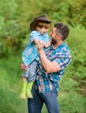Small boy child help father in farming. father and son in cowboy hat on ranch. kid in rubber boots. happy man dad in. Small boy child help father in farming stock photo