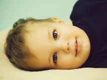 Small boy child toddler. With charming smiling positive face in black shirt laying on light and blue background closeup royalty free stock photo
