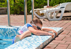 Small boy clambering out of a swimming pool Royalty Free Stock Image