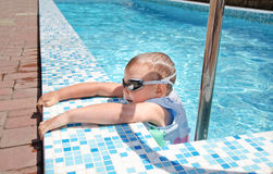 Small boy clambering out swimming pool Stock Photos