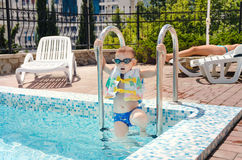 Small boy clambering out of a swimming pool. Onto the mosaic surround in his goggles and buoyancy jacket royalty free stock photography