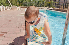 Small boy clambering out of a swimming pool Stock Photography