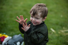 Small boy clapping his hands. Small boy smiling and clapping his hands while out of doors, well wrapped up in a brown jacket, and standing in a garden or park stock photography
