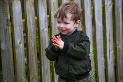 Small boy clapping. Small boy in warm black jacket zipped up clapping his hands and smiling, background of wooden garden fence stock images