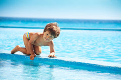 Small boy climbs on boarder of swimming pool Stock Images
