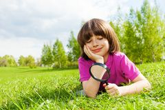 Small boy with closed eyes holds magnifier laying Stock Images