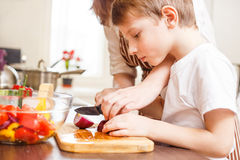Small boy cutting in slices vegetables with mother. Small boy cutting in slices vegetables for salad with his mother in the kitchen Family cooking background Royalty Free Stock Images