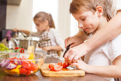 Small boy cutting in slices vegetables with mother. Small boy cutting in slices vegetables for salad with his mother in the kitchen Family cooking background Stock Images