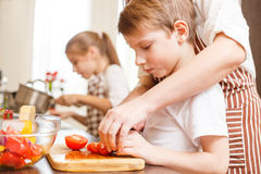 Small boy cutting in slices vegetables with mother. Small boy cutting in slices vegetables for salad with his mother in the kitchen Family cooking background Stock Photography