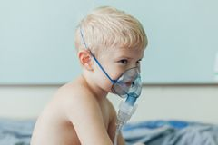 Small boy does therapeutic inhalation using a nebulizer stock photo