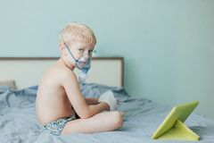 Small boy does therapeutic inhalation using a nebulizer royalty free stock photos