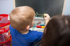 Small boy drawing on a board. A photo of small boy chalking on the blackboard. He's being watched by his teacher Royalty Free Stock Photo