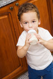 Small boy drinking milk. From a bottle in the kitchen Royalty Free Stock Image