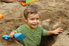 Small boy in a dug out sand hole Stock Image