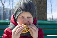 Boy is eating burger outdoor stock photography