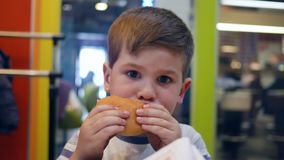 small boy eats with appetite in childrens restaurant child eating food for dinner french