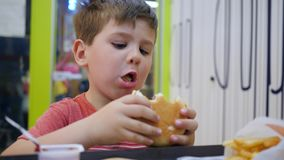small boy eats with appetite in small childrens restaurant beautiful baby eating kid plays