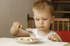 Small boy eats dinner Stock Photo