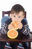 Small boy eats fresh grapefruit Royalty Free Stock Image