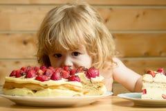Small boy eats strawberry cake Royalty Free Stock Photos