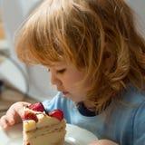 Small boy eats strawberry cake Royalty Free Stock Image