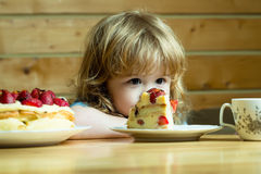 Small boy eats strawberry cake Stock Images
