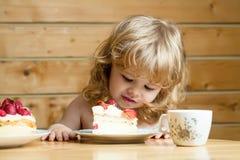 Small boy eats strawberry cake Royalty Free Stock Photo