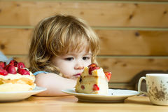 Small boy eats strawberry cake Royalty Free Stock Images