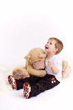Small boy embraces plush bear. And laughs, is isolated on white background Royalty Free Stock Image