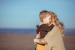 A small boy is embracing with his mum. A five-year-old boy and his mother are embracing at the seashore in a sunny day. Clothes: casual Stock Image