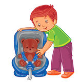 Small boy fastens his teddy bear in the children s car seat Royalty Free Stock Photography