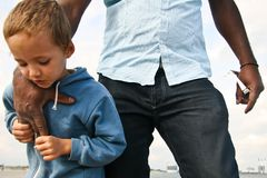 Small boy feeling safe. A small boy spending a day with family near the ocean, playing and feeling safe Stock Photo